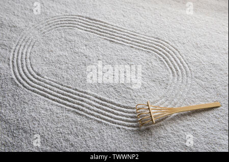 Small wooden rake sits on Japanese Zen garden raked with a simple sports running track oval in textured white sand - Stock Photo
