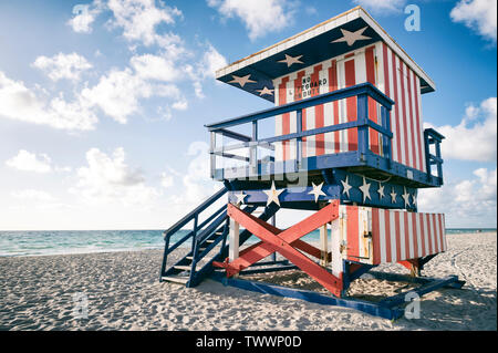 Classic red, white, and blue American flag themed lifeguard tower, now retired, on the sand in South Beach, Miami, Florida, USA - Stock Photo