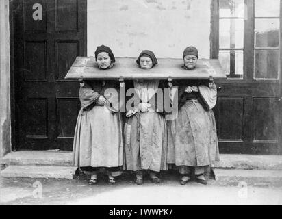 A late 19th century, or early 20th century vintage black and white photograph showing three Chinese women locked in a Cangue, a device used for public humiliation or sometimes torture in may parts of Eastern Asia. - Stock Photo