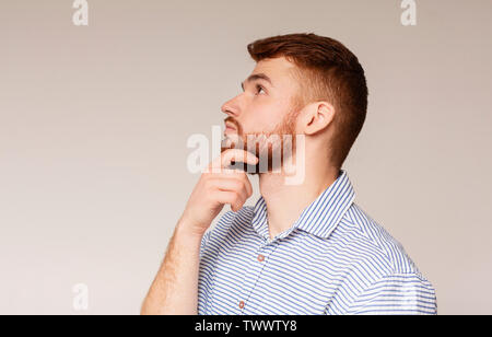 Portrait of thoughtful guy on beige background - Stock Photo