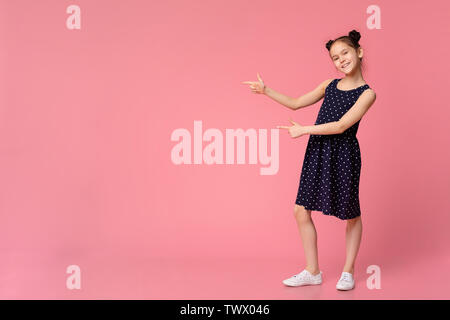 Cheerful girl in stylish dress pointing at empty space - Stock Photo