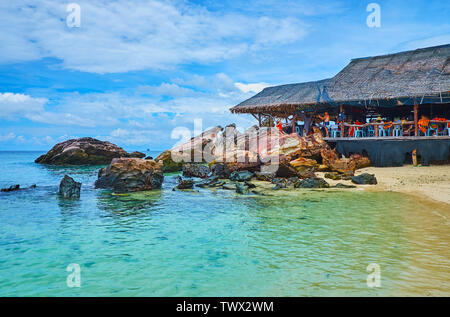 PHUKET, THAILAND - MAY 1, 2019: The old wooden hut on the shore of Khai Nai island neighbors with the huge boulders and rocks, on May 1 on Phuket - Stock Photo
