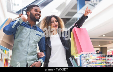 Young african couple doing shopping together in city mall - Stock Photo