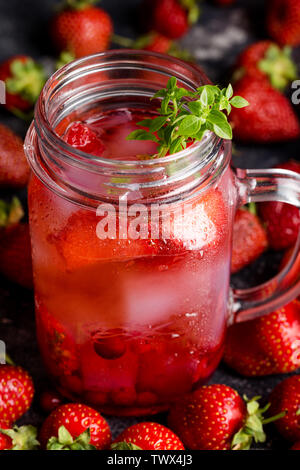 Close up strawberry lemonade with ice in jar with berries and basil around on dark background. - Stock Photo