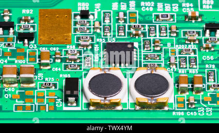 Electronic components. Coils, resistors, capacitors, transistors and chip. Electrotechnical background. Surface mount technology. Green circuit board. - Stock Photo