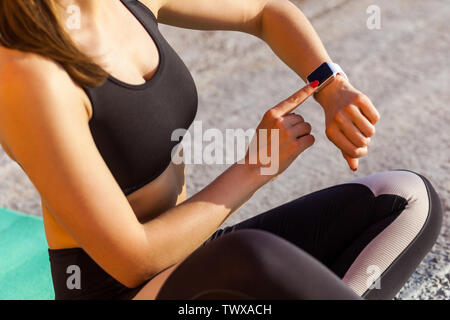 Closeup portrait of young girl wearing black sporwear practicing sport exercises in morning on street, reading message on smartwatch, checking result - Stock Photo