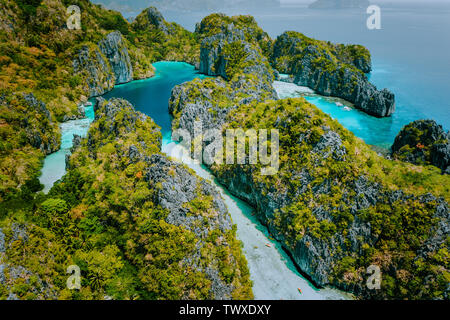 Aerial drone view beautiful shallow tropical Big and Small Lagoon explored inside by tourist on kayaks surrounded by jagged limestone karst cliffs. El