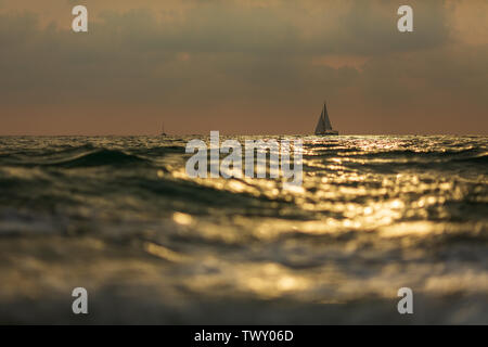 lonely sailboat in the storm at sunset - Stock Photo