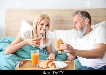 Happy elderly couple having breakfast in bed - Stock Photo