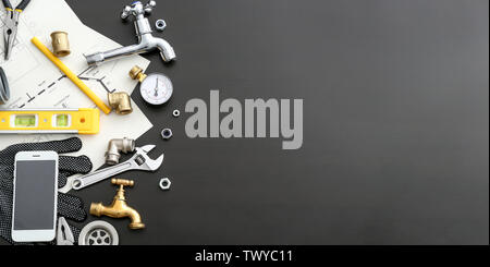 Mobile phone with plumbing items on dark background - Stock Photo
