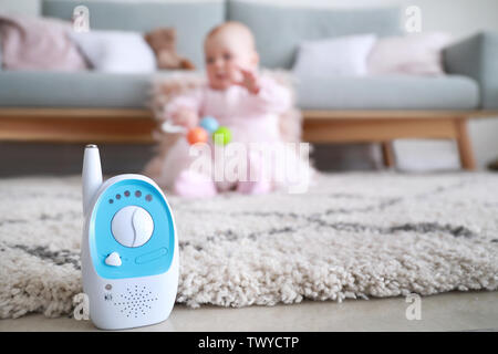 Modern baby monitor on floor in room with little child - Stock Photo