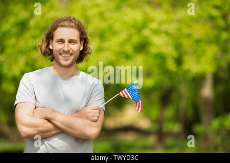 Happy young man with USA flag outdoors. Independence Day celebration - Stock Photo