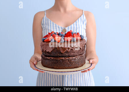 Woman holding tasty chocolate cake on light background - Stock Photo