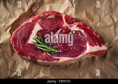 Raw ribeye beef steak with herbs and spices on a paper. Top view. Flat lay - Stock Photo