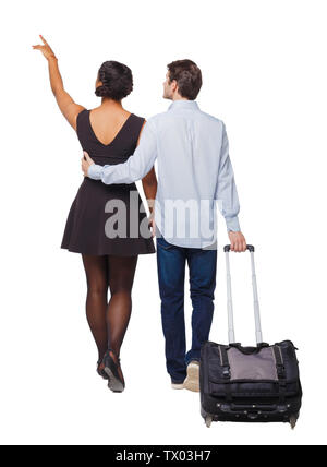 Back view of pointing interracial going couple with suitcase. Rear view people collection. backside view of person. Isolated over white background. Yo - Stock Photo