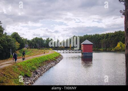 A small red hut built on a river and connected to a bridge with amazing natural scenery and a cloudy sky - Stock Photo
