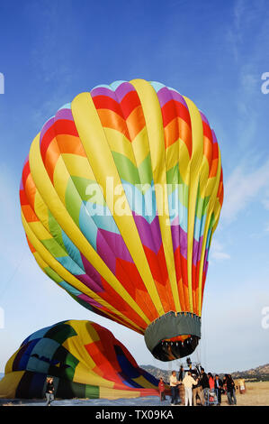 Passengers load into a coloful hot air baloon as the crew readies it for takeoff in Napa Valley, California, USA. - Stock Photo