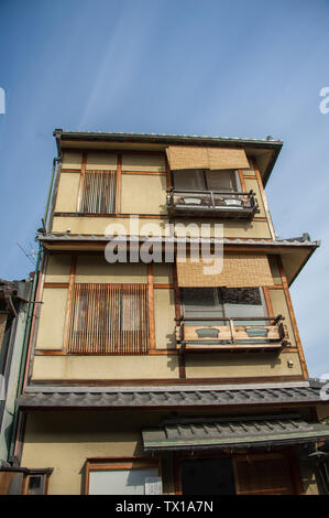 Kyoto, Japan - April 2019: Traditional Edo-style apartment housing in the Gion District. Tri-level buildng with blue sky background - Stock Photo