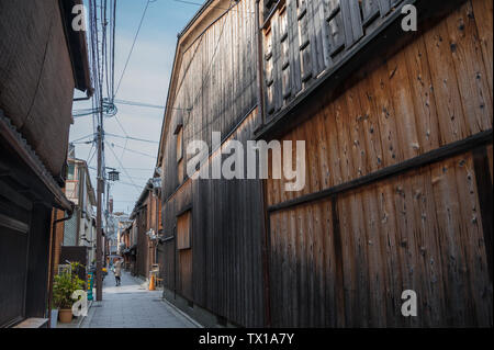 Traditional Edo-style architecture in the Gion District. Woman with umbrella walks along narrow street lined with wooden buildings - Stock Photo