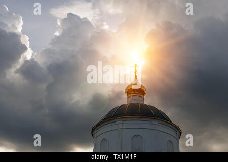 Sun rays make their way through the thunderclouds illuminating the golden cross on the dome of the old church
