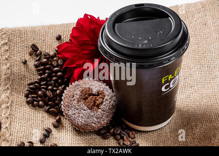 Coffee to go concept. Cup with coffee, muffin, red flower and coffee beans on a jute bag with a white background. - Stock Photo