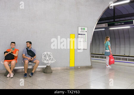 Passengers waiting for a train at the Fovam ter metro station on M4 line in Budapest, Hungary. - Stock Photo