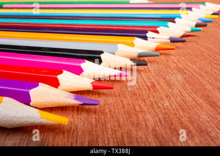 A neatly arranged colored pencil on a wooden board. - Stock Photo