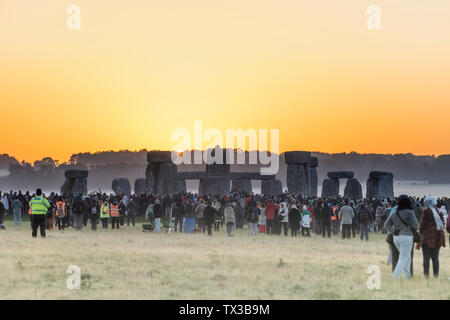 The 2019 Summer Solstice at Stonehenge, Wiltshire, UK, sees a crowd in its thousands wait for and watch the sun rise on the longest day. - Stock Photo
