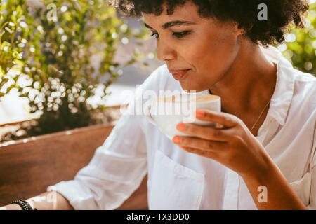 Close up of young african woman writing and having coffee. Female with coffee siting at outdoors cafe and making notes.