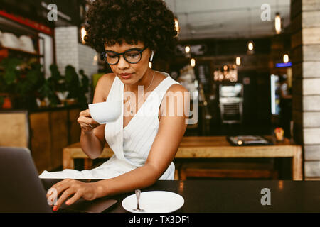 Young woman sitting in cafe working on laptop and drinking coffee. African woman having coffee while working on laptop computer in coffee shop.