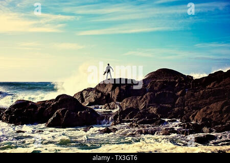 Silhouette male surfer watching ocean waves crash against rocks on sunny beach, Tofino, Canada - Stock Photo