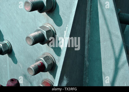 Bolts and nuts on metal surface, top view - Stock Photo