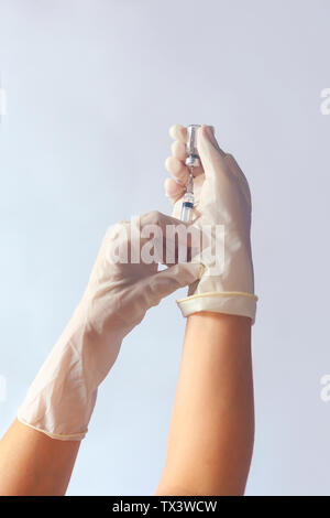 A nurse hands in glove with syringe and medicine. Medical, immunization and vaccination concept. Syringe in hand - Stock Photo