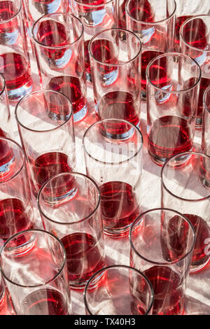 Summertime in Britain - glasses of Campari poured ready for a summer garden party, waiting to have soda added to make a Campari & soda cocktail - Stock Photo