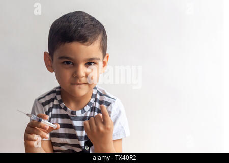 A little bad boy holding the syringe and calling someone with his finger. A child having fun at the hospital. - Stock Photo