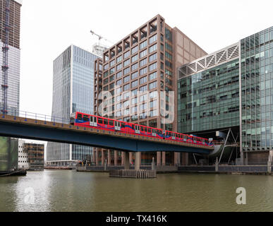 Canary Wharf, London - a Docklands Light Railway train emerges from Heron Quays station to cross a bridge over South Dock. - Stock Photo