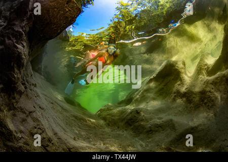 Austria, Salzkammergut, young woman snorkeling in mountain river Weissenbach