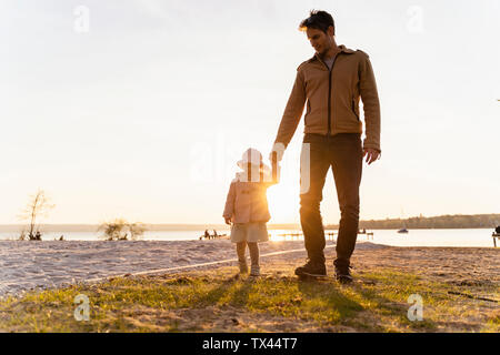 Germany, Bavaria, Herrsching, father and daughter walking at the lakeshore at sunset - Stock Photo