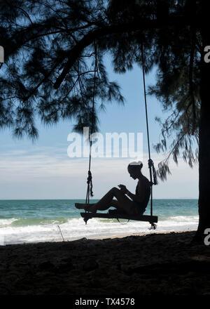 Thailand, Krabi, Lao liang island, woman on tree swing on the beach - Stock Photo