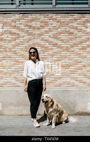 Laughing woman standing besides her Labrador Retriever in front of patterned brick wall - Stock Photo