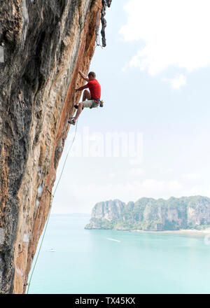 Thailand, Krabi, Thaiwand wall, man climbing in rock wall above the sea - Stock Photo