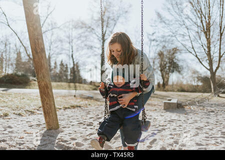 Mother with little daughter on swing on a playground