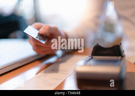 Customer paying bill with credit card, close-up - Stock Photo