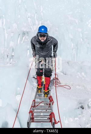 Nepal, Solo Khumbu, Everest, Mountaineer climbing on icefall - Stock Photo