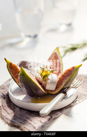 Figs and goat cheese, rosemary, pouring with honey - Stock Photo