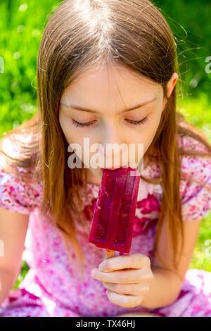Portrait of girl eating popsicle in garden - Stock Photo