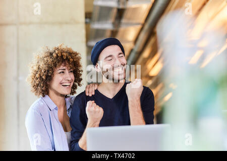 Excited man and woman with laptop in modern office - Stock Photo