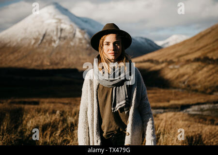 UK, Scotland, Loch Lomond and the Trossachs National Park, portrait of young woman wearing a hat in rural landscape Stock Photo