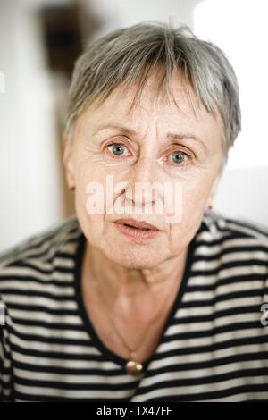 Portrait of senior woman with short hair, respectable looking in camera - Stock Photo