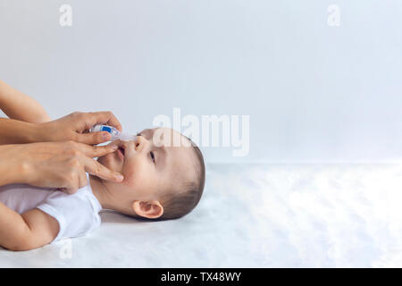 Mother put saline drops in infant's nose. Little boy getting nasal drops. 6-month baby boy gets nose drops. Pediatrician putting saline drops in infan - Stock Photo